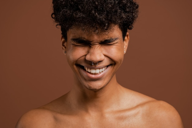 Foto van aantrekkelijke zwarte man met doordringende glimlach met gesloten ogen. naakte torso, geïsoleerde bruine kleurenachtergrond.