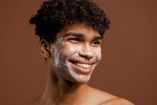 Foto van aantrekkelijke zwarte man met doordringende glimlach met voedingsmasker op gezicht, mooie glimlach en tanden. naakte torso, geïsoleerde bruine kleurenachtergrond.