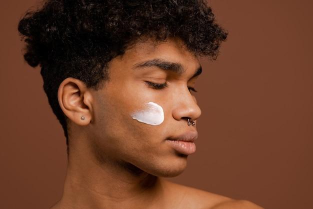 Foto van aantrekkelijke zwarte man met piercing en voedingscrème op gezicht. naakte torso, geïsoleerde bruine kleurenachtergrond.