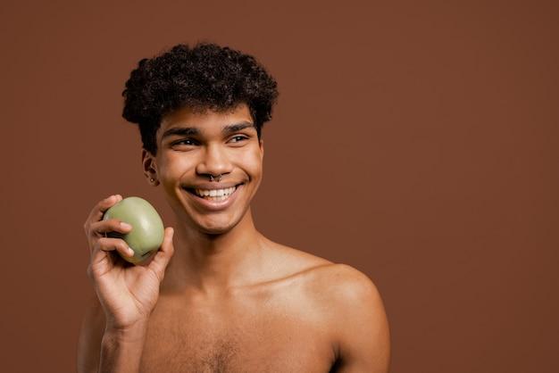 Foto van aantrekkelijke zwarte man met piercing houdt appel en glimlacht. naakte torso, geïsoleerde bruine kleurenachtergrond.