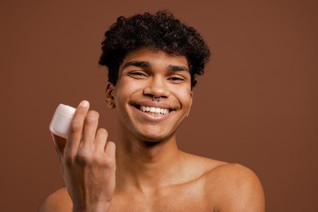 Foto van aantrekkelijke zwarte man met piercing houdt voedingsroom en glimlacht met witte tanden. naakte torso, geïsoleerde bruine kleurenachtergrond.