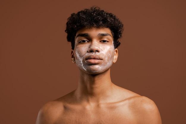 Foto van aantrekkelijke zwarte man met piercing kijkt naar camera met voedingsmasker op gezicht. naakte torso, geïsoleerde bruine kleurenachtergrond.