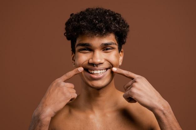 Foto van aantrekkelijke zwarte man met piercing laten zien hoe breed zijn glimlach is. naakte torso, geïsoleerde bruine kleurenachtergrond.