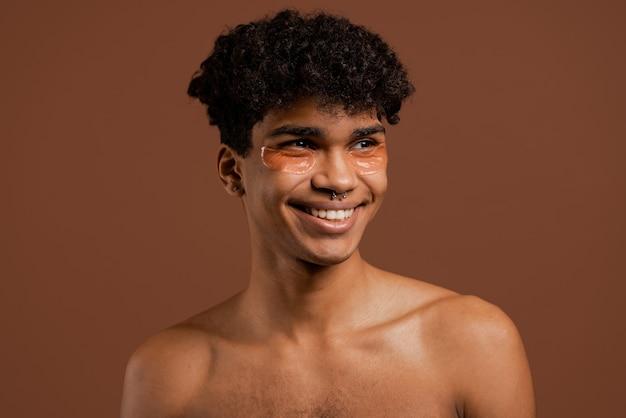 Foto van aantrekkelijke zwarte man met piercing met ooglapjes op glimlacht. naakte torso, geïsoleerde bruine kleurenachtergrond.
