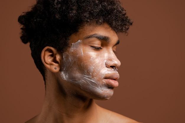 Foto van aantrekkelijke zwarte man met piercing met voedingsmasker op gezicht. naakte torso, geïsoleerde bruine kleurenachtergrond.