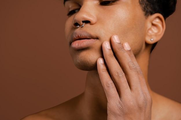 Foto van aantrekkelijke zwarte man met piercing raakt zijn gladde gezicht. naakte torso, geïsoleerde bruine kleurenachtergrond.
