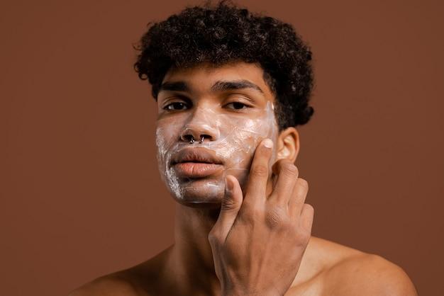 Foto van aantrekkelijke zwarte man met piercing zet crème of voedingsmasker op gezicht. naakte torso, geïsoleerde bruine kleurenachtergrond.
