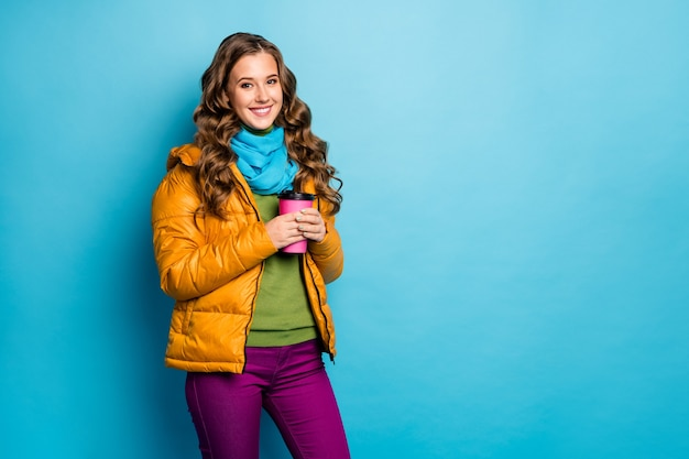 Foto van aardige dame houdt warm papier drank mok geniet van herfst weer draag casual gele overjas sjaal violet broek groene trui geïsoleerde blauwe kleur muur