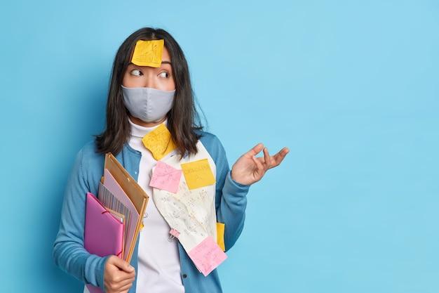 Foto van aarzelende aziatische vrouw haalt haar schouders op, weet niet hoe ze werk moet maken, draagt beschermend masker tijdens coronavirus-pandemie.