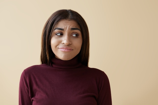 Foto van aarzelende jonge gemengd ras vrouw met donker lang haar fronsend en zijwaarts kijkend met perplex twijfelachtige gezichtsuitdrukking