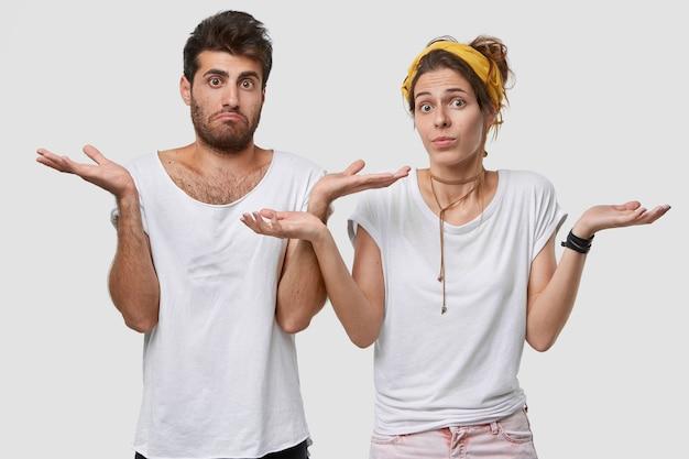 Foto van aarzelende vriend en vriendin kijken met onzekerheid, ontvangen suggestie, hebben twijfelachtige gezichtsuitdrukkingen, draagt wit t-shirt in één toon met muur