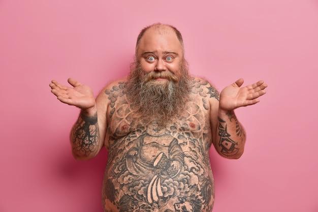 Foto van aarzelende vrolijke man spreidt zijn handpalmen zijwaarts, zegt dat ik het niet weet, gelukkig en verward is, een grote buik heeft, een getatoeëerd lichaam heeft, niet weet hoe hij fit moet zijn en afvallen, geïsoleerd op een roze muur