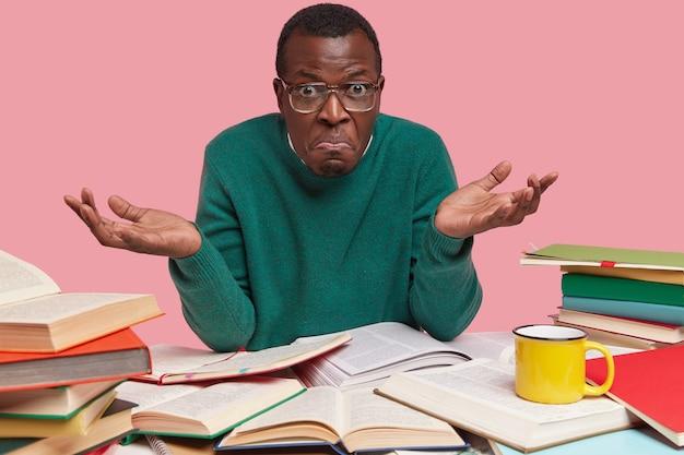 Foto van aarzelende zwarte man kijkt met geen idee van uitdrukking, kan geen onderwerp kiezen voor cursuspapier, zoekt naar universitaire test