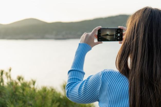 Foto van achteren van vrouw die selfie maakt van eiland met zonsondergang