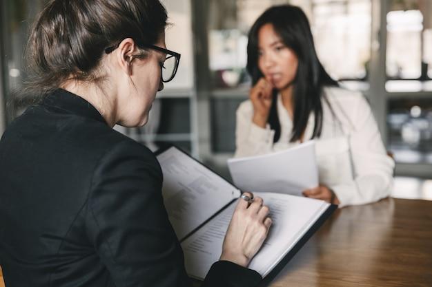Foto van achterkant serieuze zakenvrouw interviewen, en praten met gespannen vrouwelijk personeel tijdens sollicitatiegesprek - business, carrière en plaatsing concept