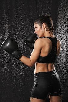 Foto van achterkant van energieke vrouw boksen met handschoenen en staande in de aanvalspositie onder regendruppels, geïsoleerd op zwarte achtergrond