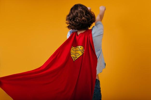 Foto van achterkant van krachtige supergirl geïsoleerd op gele ruimte