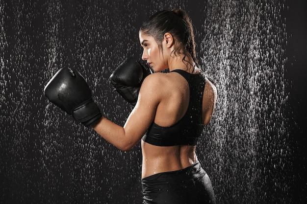 Foto van achterkant van sportieve meisje 20s in sportkleding en bokshandschoenen stoten stoten onder regendruppels, geïsoleerd op zwarte achtergrond