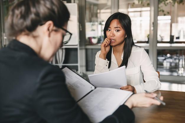 Foto van achterkant van zakenvrouw interviewen, en het lezen van cv van nerveuze vrouwelijke sollicitant tijdens sollicitatiegesprek - concept van zaken, carrière en plaatsing