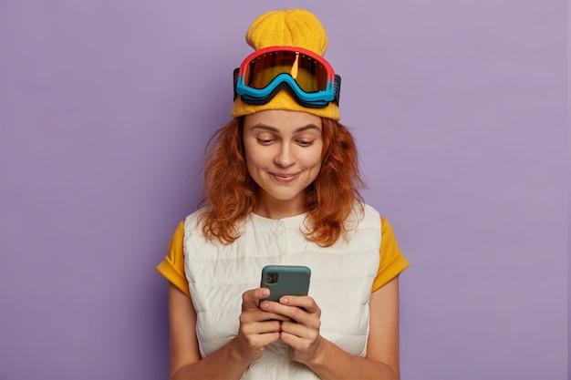 Foto van actieve roodharige tienermeisje maakt gebruik van mobiele telefoon om online te chatten, brengt wintervakantie door in de bergen, draagt snowboard beschermend masker, geniet van reizen en gratis internetverbinding