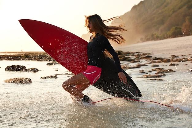 Foto van actieve surfer springt in water van geluk, heeft tijd voor haar favoriete hobby