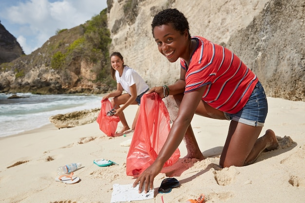 Foto van actieve verantwoordelijke vrijwilligers verzamelen zwerfvuil op zandstrand