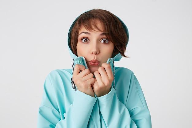 Foto van afgevraagd jonge mooie vrouw in blauwe regenjas, met een kap op zijn hoofd, kijkt naar de camera met verrassende uitdrukkingen, staat over een witte muur.