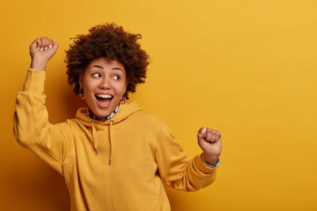 Foto van afrikaans amerikaans meisje doet geluksdans, steekt handen omhoog in hoera, voelt zich als kampioen na triomf, staart gelukkig ergens, heeft plezier, voelt ritme van muziek, geïsoleerd op gele muur