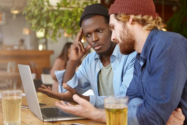 Foto van afro-amerikaanse man met laptopcomputer tijdens een ontmoeting met zijn blanke zakenpartner in café voor het bespreken van bedrijfsstrategie en plannen voor een paar biertjes, mensen en technologie