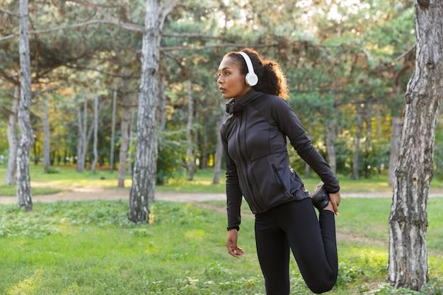 Foto van afro-amerikaanse sportvrouw 20s, gekleed in zwart trainingspak sporten, en lichaam uitrekken in groen park