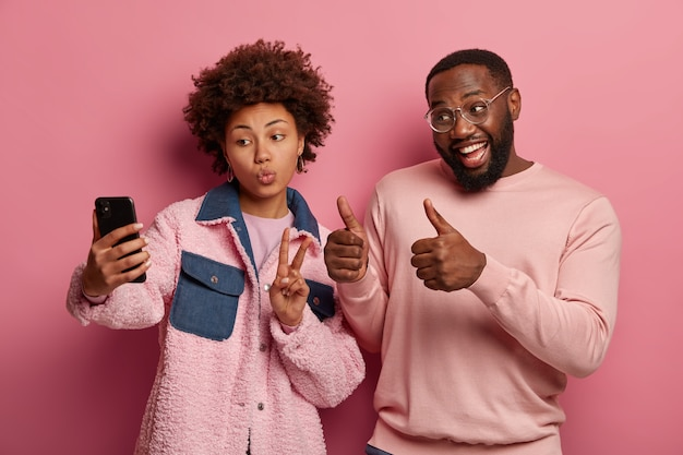 Foto van afro-amerikaanse vrouw en man nemen selfie-portret op mobiel, maakt vrede en hou van gebaren, kijk positief naar smartphonecamera, draag roze kleding