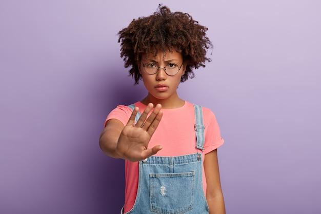 Foto van afro-amerikaanse vrouw stopt gebaar, heeft boze gezichtsuitdrukking, eist stoppen met praten, toont verbod zonder teken, kijkt boos door ronde bril,