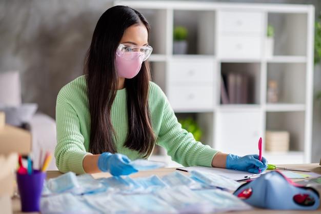 Foto van aziatische dame werk familiebedrijf bestellingen organiseren gezicht griep medische maskers wereldwijde verspreiding schrijven lezen klanten informatie voorbereiden van pakketten voor levering thuis blijven quarantaine binnenshuis