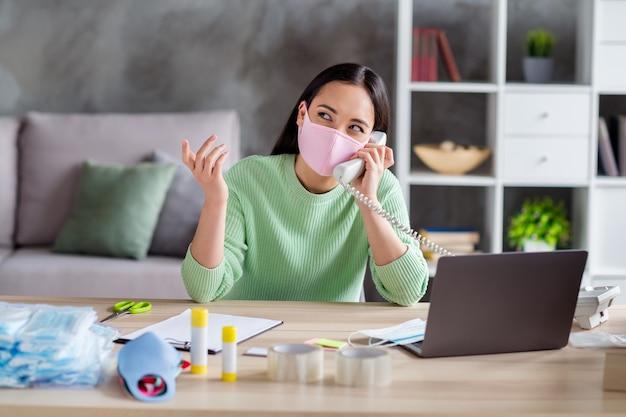Foto van aziatische drukke zakenvrouw die medische maskers voor gezichtsgriep organiseert voor het afleveren van dozen sprekend ophalen vaste lijn klant schrijven klembord besteldetails thuiskantoor binnenshuis
