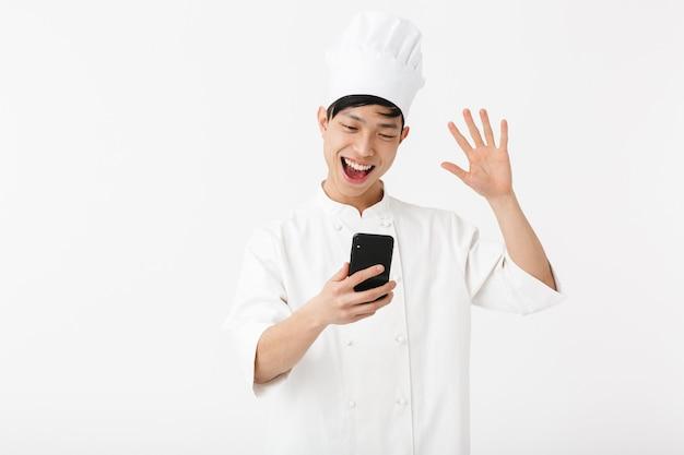 Foto van aziatische hoofdman in witte uniforme kok en koksmuts die mobiele telefoon houdt die over witte muur wordt geïsoleerd