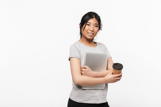 Foto van aziatische mooie jonge vrouw poseren geïsoleerd over witte muur koffie drinken met laptopcomputer.