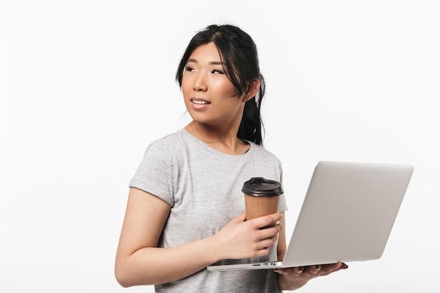 Foto van aziatische mooie jonge vrouw poseren geïsoleerd over witte muur met behulp van laptopcomputer koffie drinken.