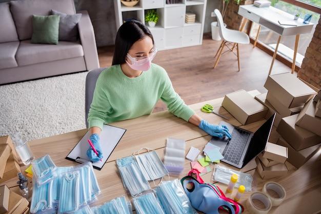 Foto van aziatische zakendame organiseren lezen schrijven notitieboekje bestellingen manager gezichtsgriepmaskers product internetservice leveringspakket voorbereiden veiligheid thuiskantoor quarantaine binnenshuis