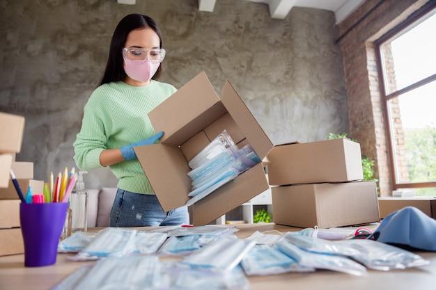 Foto van aziatische zakenvrouw kreeg internetbestelling postmanager gezichtsmaskers product internetservice grote doos die ademhalingstoestellen desktop wil remake nieuw creatief ontwerp thuiskantoor binnenshuis