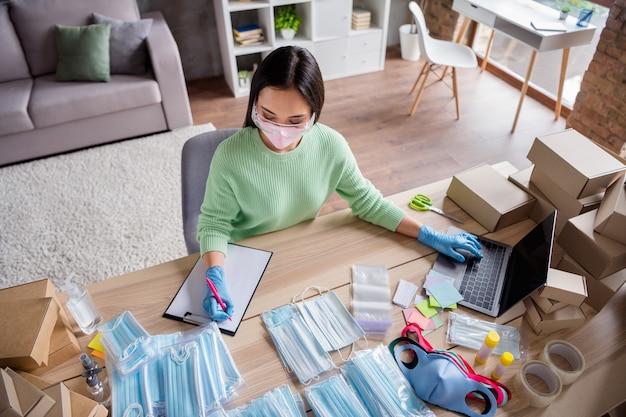 Foto van aziatische zakenvrouw organiseren lezen schrijven notitieboekje bestellingen manager gezichtsgriep modemaskers product internetservice leveringspakket voorbereiden veiligheid thuiskantoor quarantaine binnenshuis