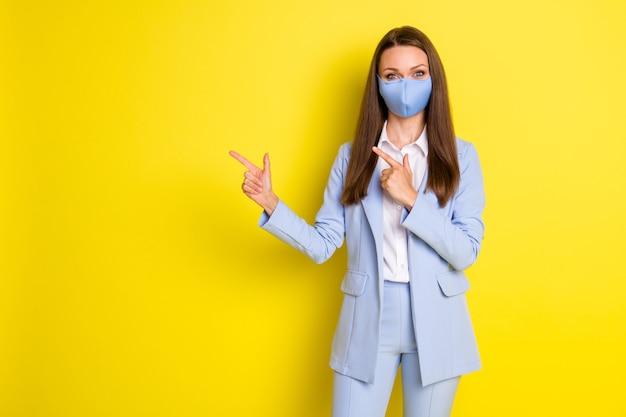 Foto van baas uitvoerend zakenvrouw punt wijsvinger copyspace aanwezig covid advertenties promotie draag blauwe jas blazer broek broek medisch masker geïsoleerd heldere glans kleur achtergrond
