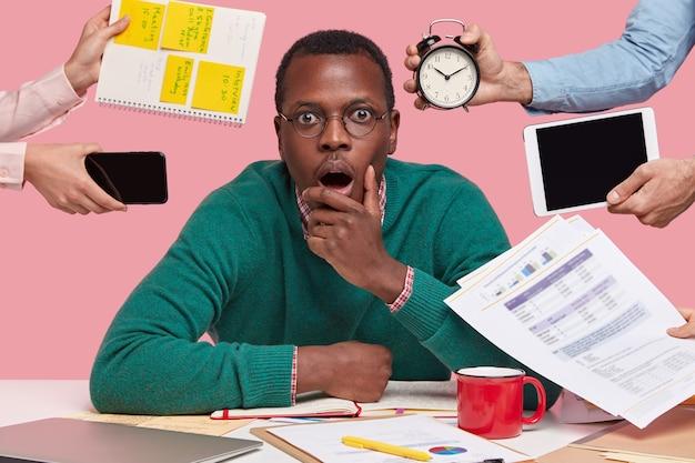 Foto van bang donkerhuidige man houdt kin, opent mond wijd, draagt een bril, omringd met mensenhanden met elektronische gadgets