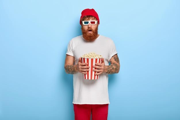 Foto van bang gember man kijkt naar nieuwe horrorfilm in de bioscoop, eet popcorn