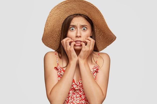 Foto van bange bange blanke vrouw met groene ogen, klemt tanden van angst, houdt handen dichtbij de mond