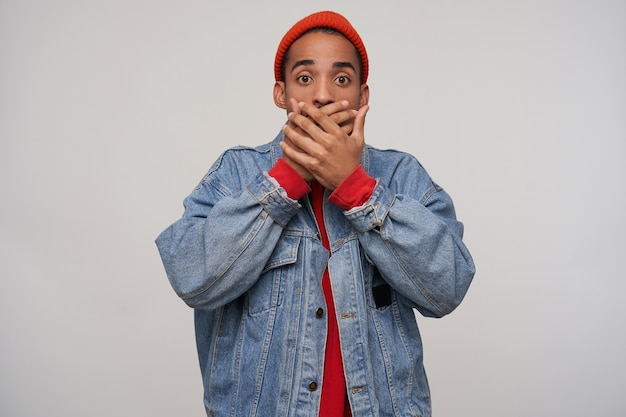 Foto van bange jonge bruinogige donkerhuidige bebaarde man die zijn mond bedekt met opgeheven handpalmen terwijl hij bang kijkt, staande tegen een witte muur