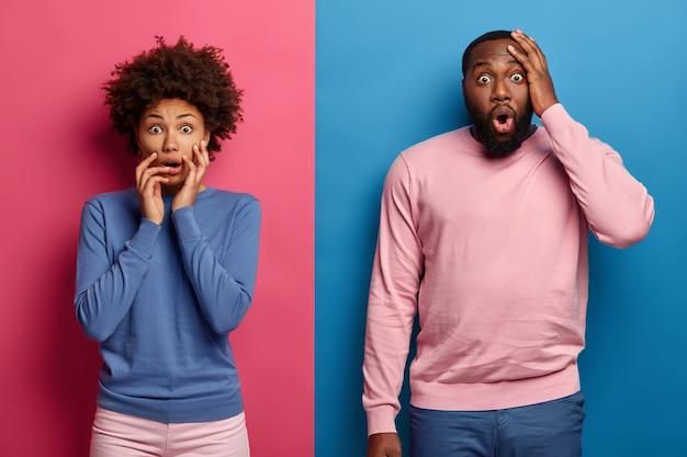 Foto van bange, overweldigde, donkere vrouw en man kijken samen naar horrorfilm, dragen blauwe en roze kleding, beven van angst