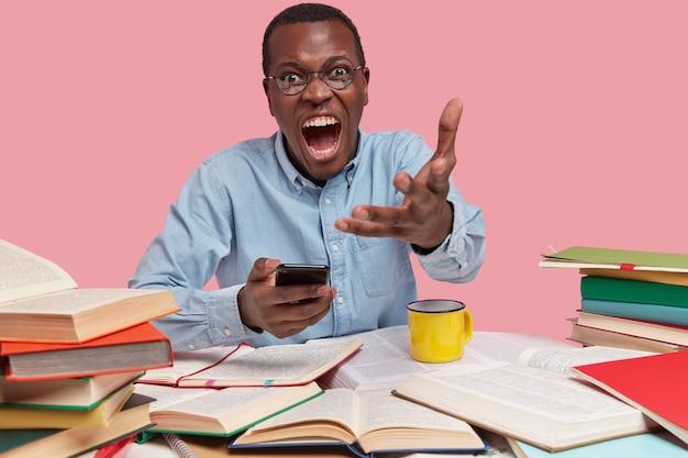 Foto van bazige man schreeuwt boos en gebaren van ergernis, houdt moderne mobiele telefoon, formeel gekleed