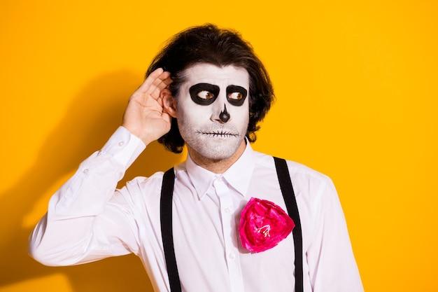 Foto van beangstigend monster met haren man hand oor afluisteren privé vertrouwelijk bericht draag wit overhemd roos suiker schedel dood kostuum bretels geïsoleerde gele kleur achtergrond