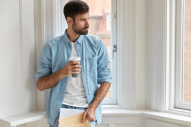 Foto van bebaarde administratieve mamager houdt papieren, wegwerp kopje koffie