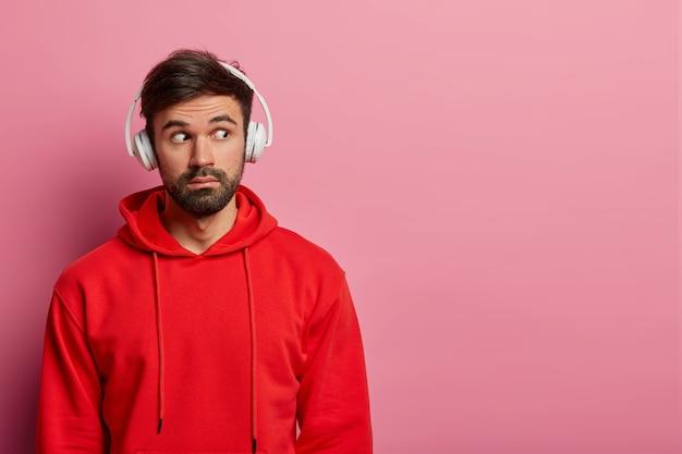 Foto van bebaarde hipster-man kijkt weg met verbaasde verwonderde blik, gekleed in rood sweatshirt, ziet iets ongelooflijks, gebruikt koptelefoon, geïsoleerd over roze pastel muur, kopieer ruimte opzij